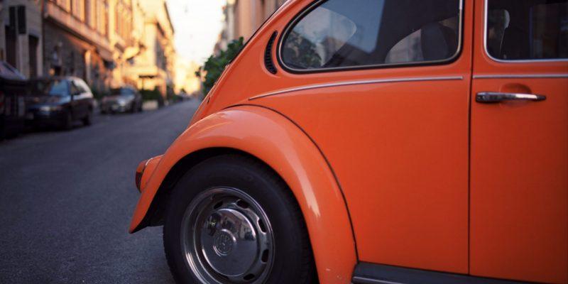 Ein orangefarbenes Aut0 steht quer auf der Straße.